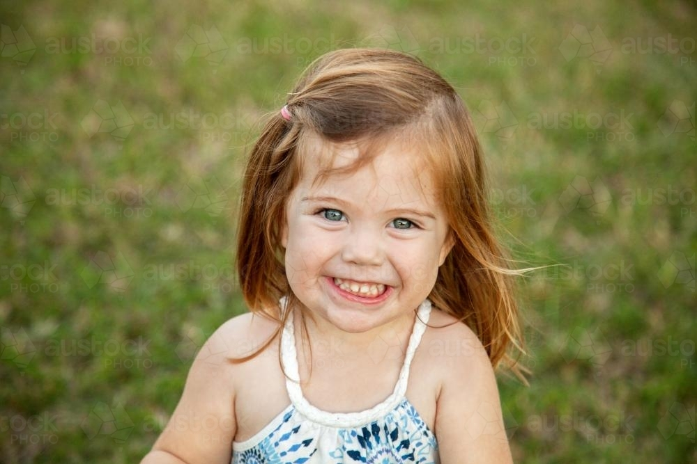 Close up of a happy little girl grinning - Australian Stock Image