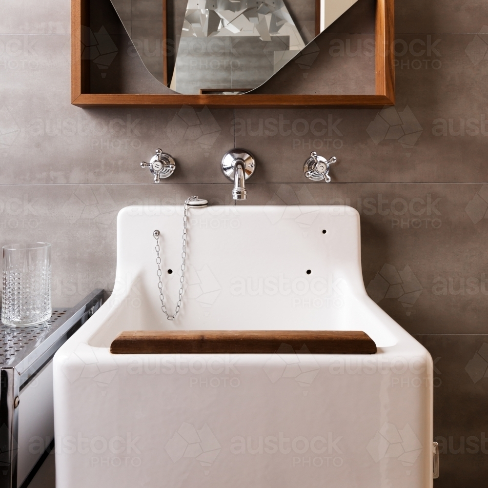 Close up of a vintage style bathroom sink with wood detail - Australian Stock Image