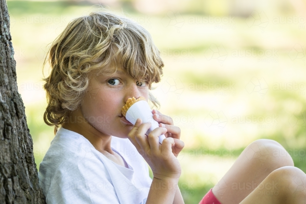 Close up of a young boy biting an ice cream cone - Australian Stock Image