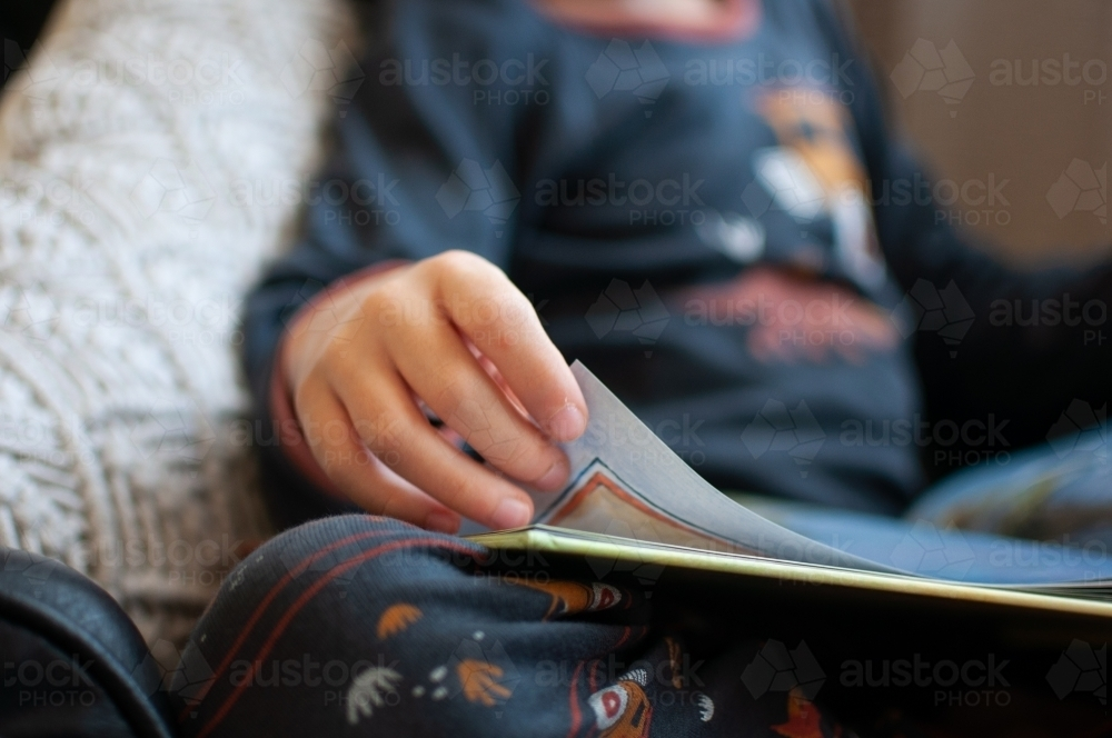 Close up of child's hand turning page of book - Australian Stock Image