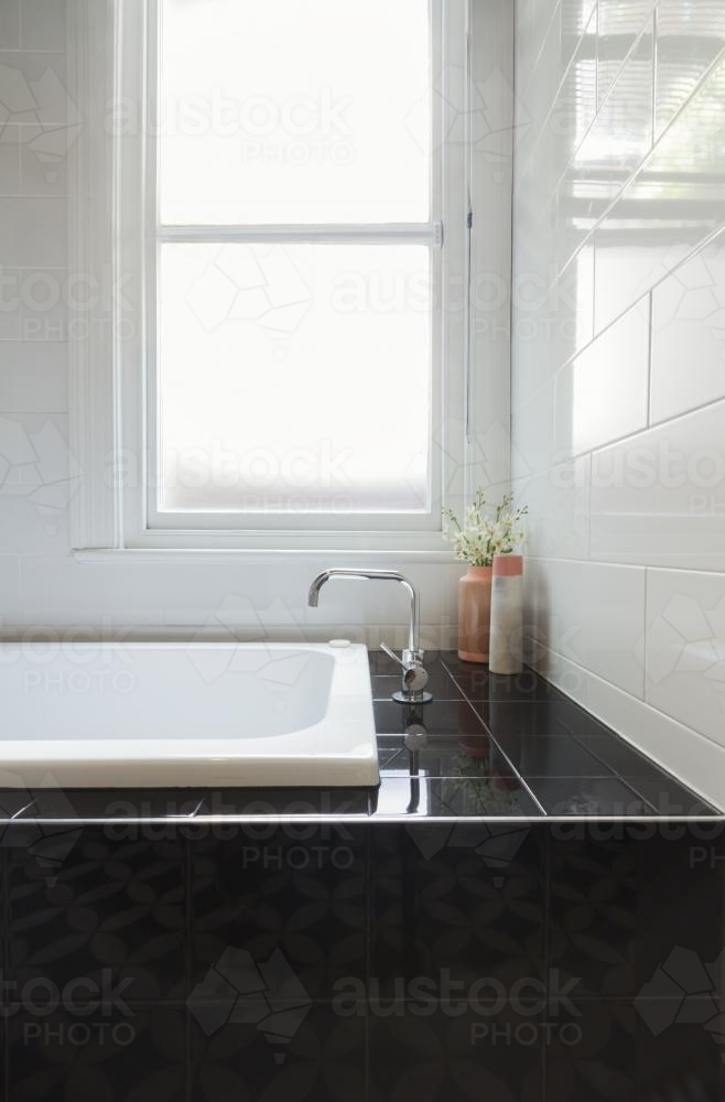 Image of Close up of designer black tiled bath hob with white tiled ...