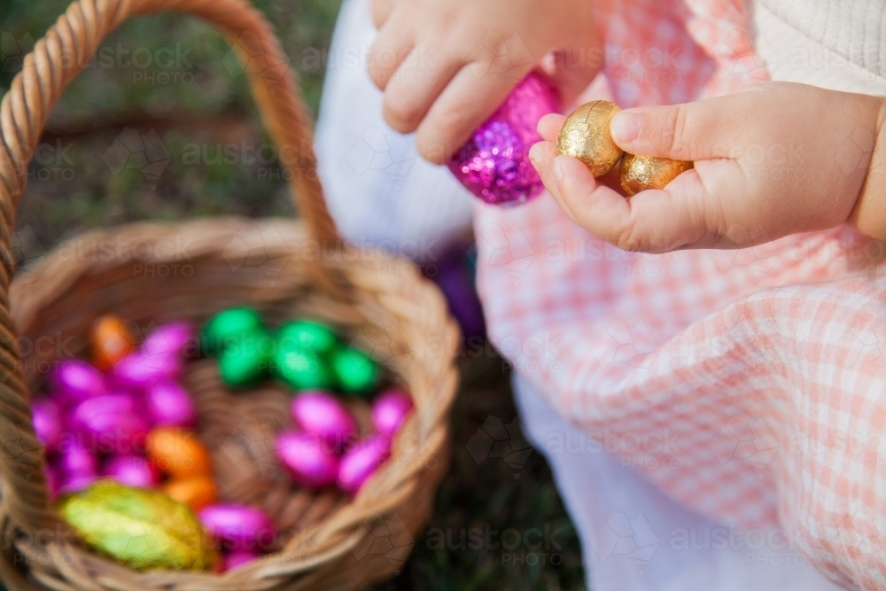 Close up of little girl taking coloured Easter eggs out of Easter egg hunt basket - Australian Stock Image