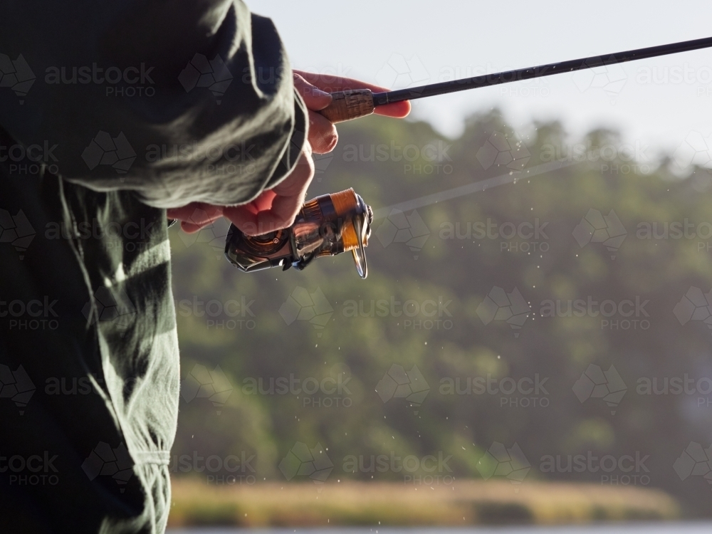 Close up of Man winding Fishing Reel while Holding a Rod - Australian Stock Image