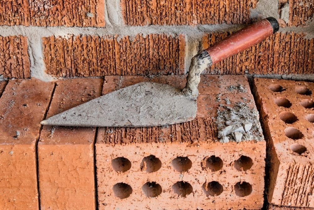 Close-up of rugged brick wall with loose bricks & trowel on building site - Australian Stock Image