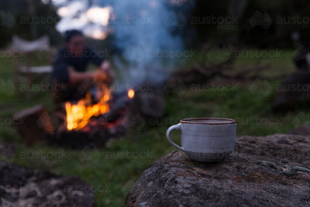 Close up of tea with man tending to campfire in background on rural property - Australian Stock Image