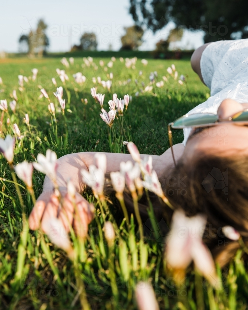 Close up of young girl lying on her back in a field of flowers - Australian Stock Image