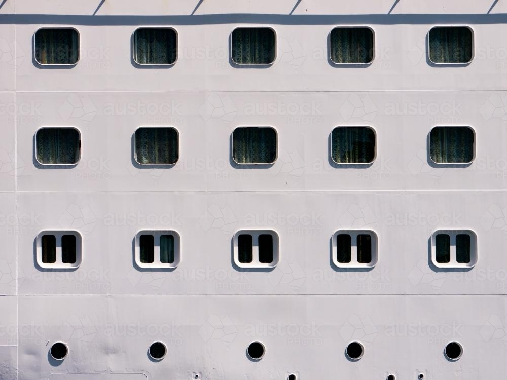 Closeup of rows of windows and portholes in a ship - Australian Stock Image