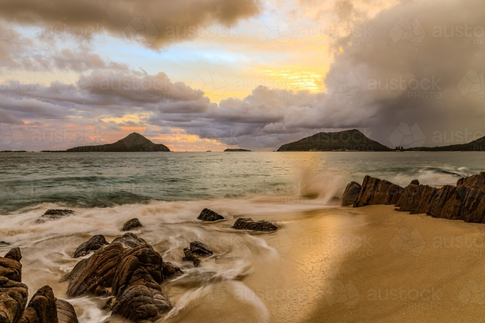 Cloudy sunrise over mountains and rocky beach - Australian Stock Image