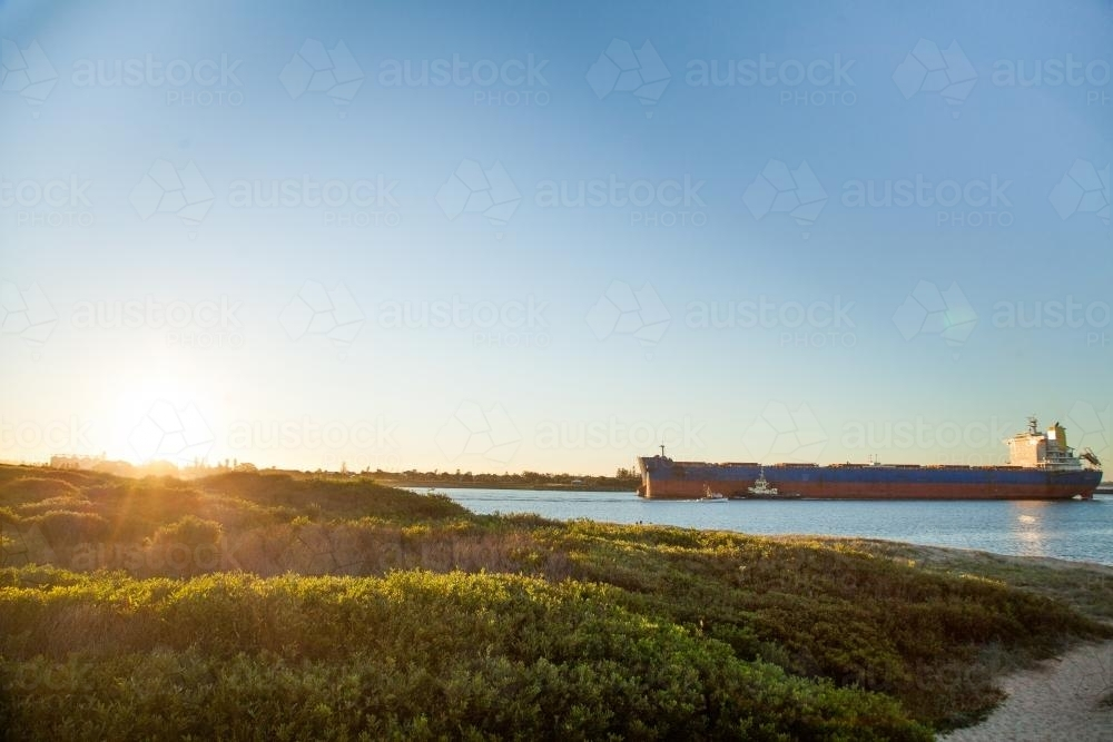 Coal ship coming into Newcastle Harbour at sunset - Australian Stock Image