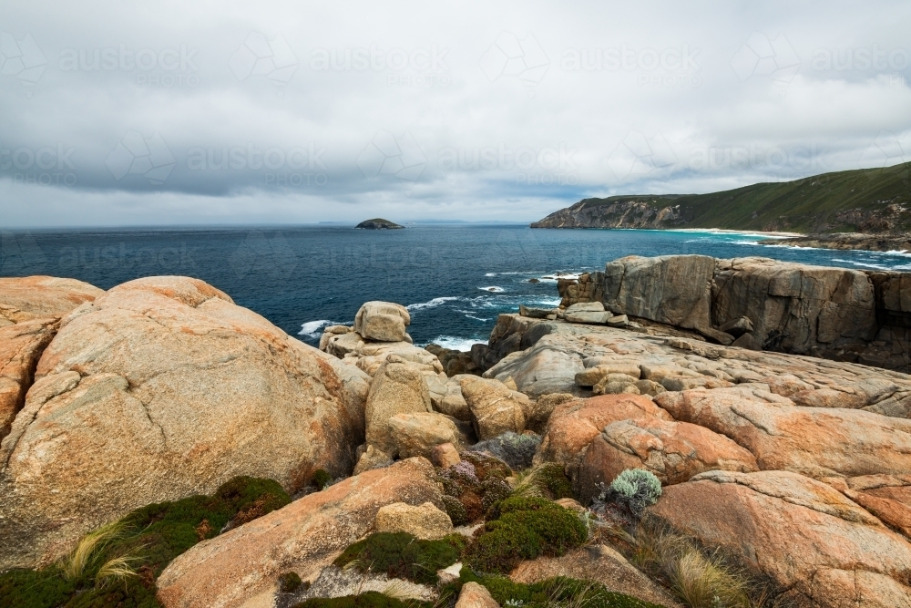Colourful rocky foreshore on Southern Ocean with stormy sky - Australian Stock Image