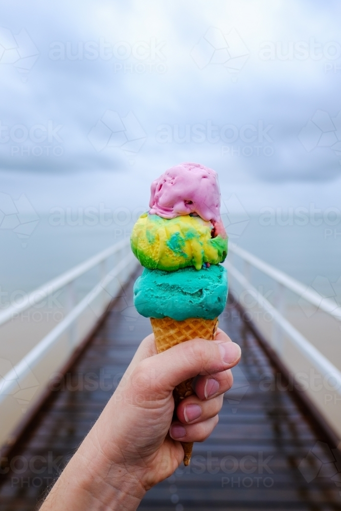 Colourful triple scoop ice cream on a jetty at Hervey Bay - Australian Stock Image