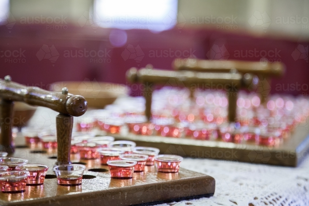 Image of Communion cups of juice in trays and bread for a