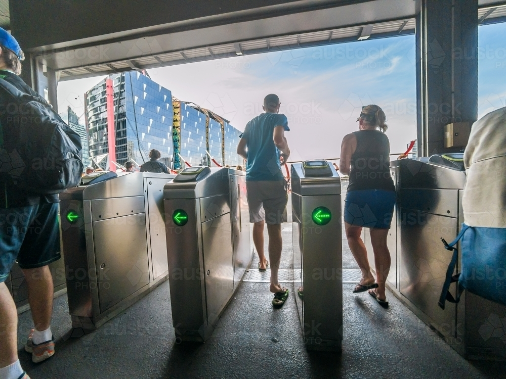 Commuters rushing through entrance barriers at a railway stations - Australian Stock Image