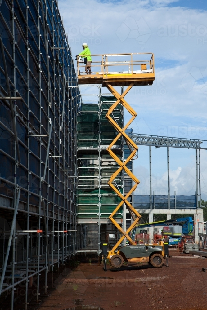 Image of Construction worker on a scissor lift on an industrial