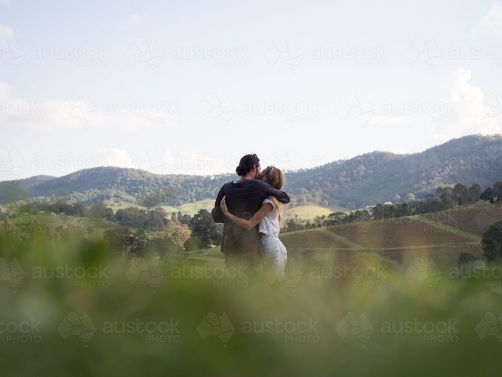 Couple cuddling whilst enjoying the view in Hunter Valley - Australian Stock Image