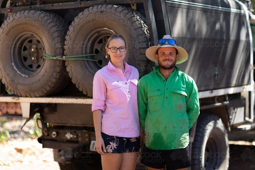 couple standing beside their 4WD vehicle on outback trip - Australian Stock Image