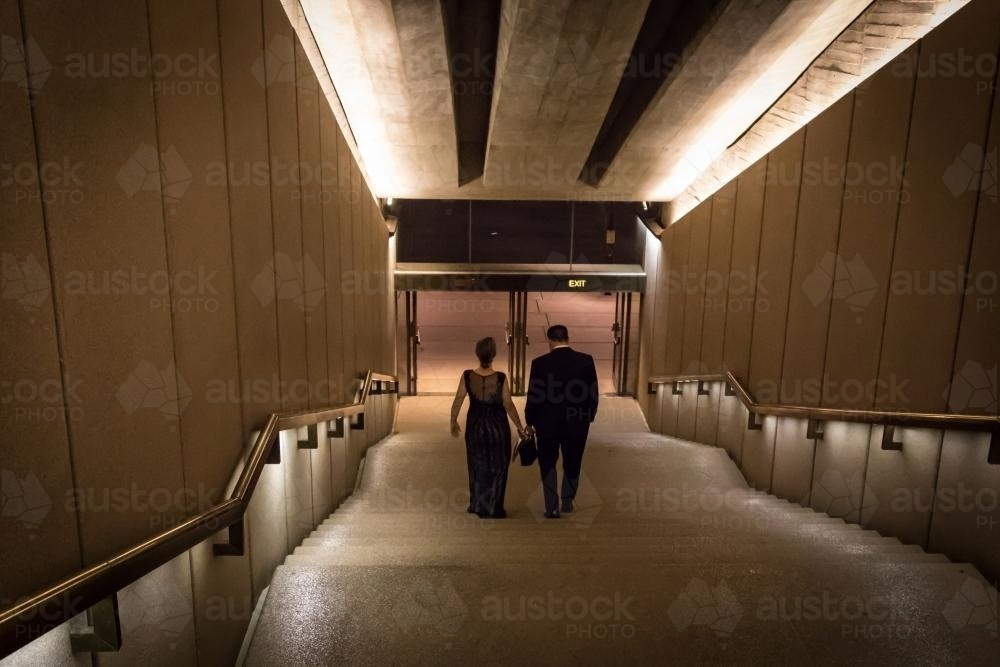 Couple walking down dark stairs after the theatre - Australian Stock Image