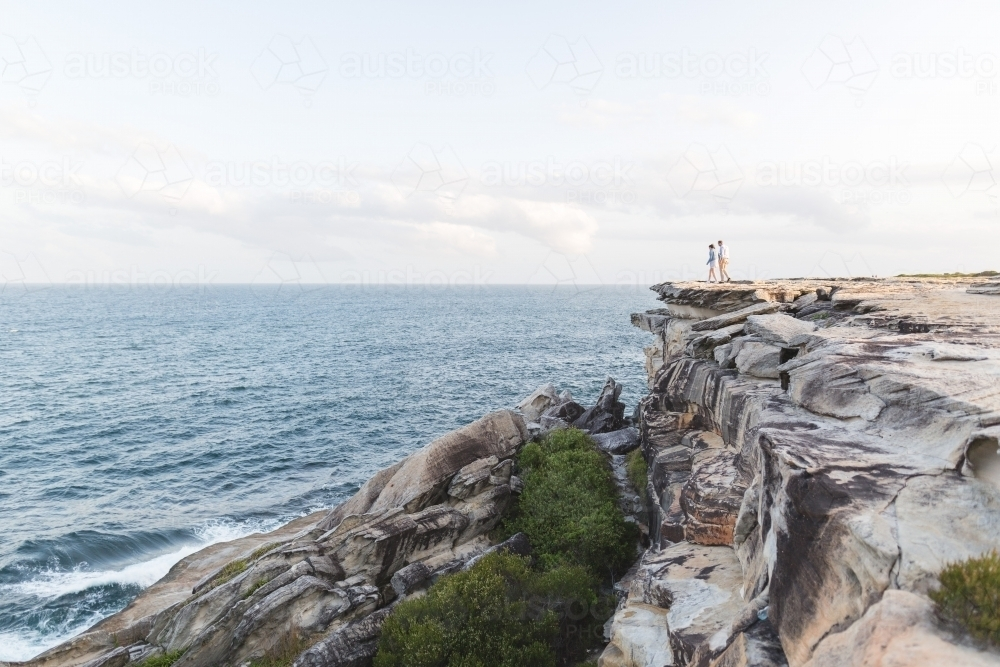 Couple walking toward edge of cliff overlooking ocean - Australian Stock Image
