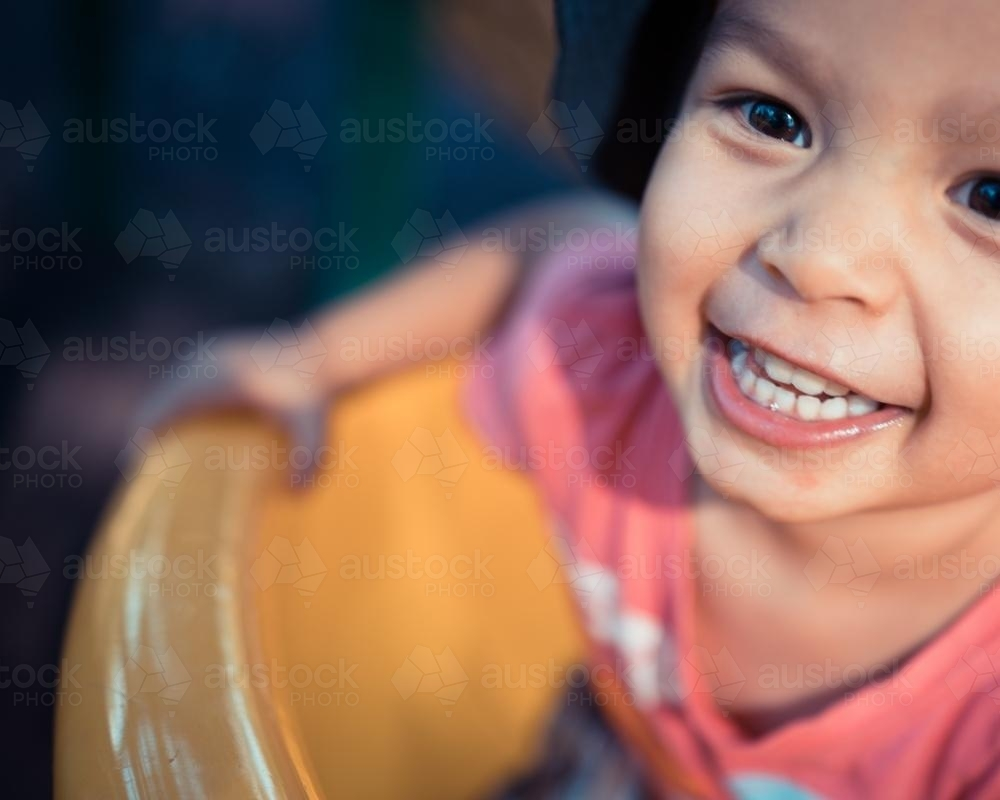Cute 3 year old mixed race boy plays cheerfully on a playground slide - Australian Stock Image