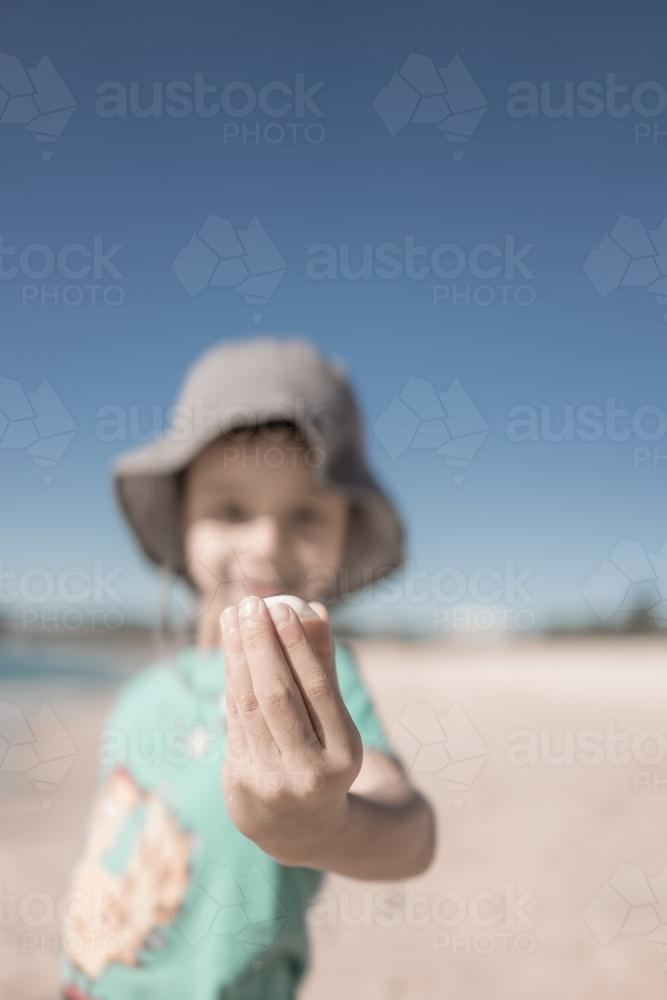 Cute 6 year old boy plays happily in the water and with shells on a Port Stephens beach - Australian Stock Image