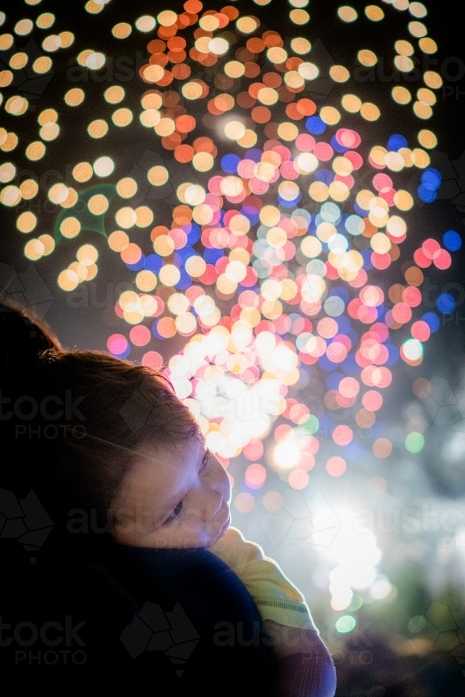 Cute mixed race baby boy cuddles his parent while new year's fireworks explode in background - Australian Stock Image