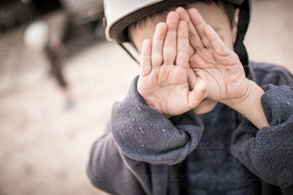 Cute mixed race boy hides behind his hands outside wearing a riding helmet - Australian Stock Image