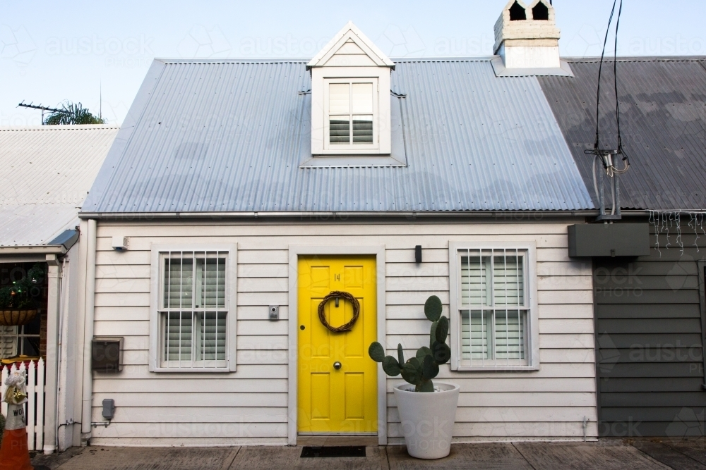 Cute white weatherboard cottage with yellow door and cactus in paddington, sydney - Australian Stock Image