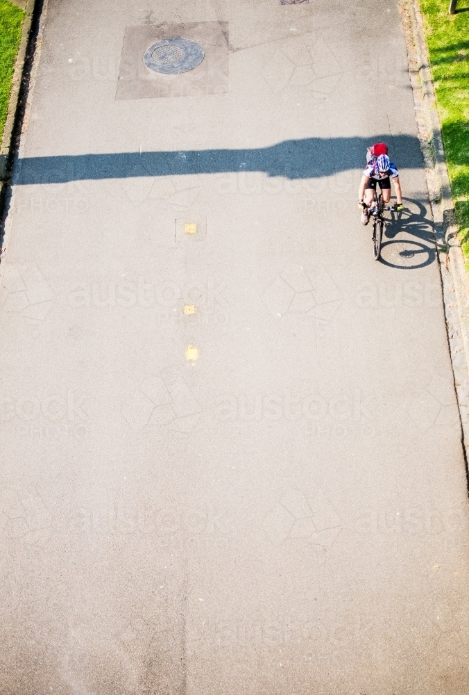 Cyclist riding on city pathway from above - Australian Stock Image