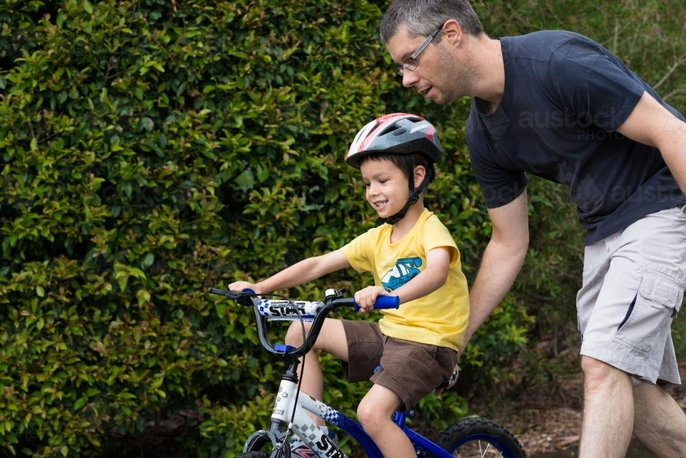 Dad teaching his son to ride a bike - Australian Stock Image