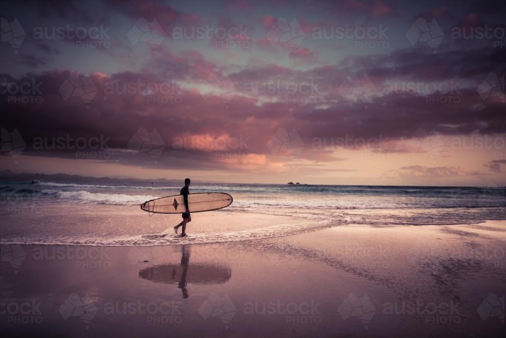 Dawn surfer at the beach in Byron Bay (high iso) - Australian Stock Image