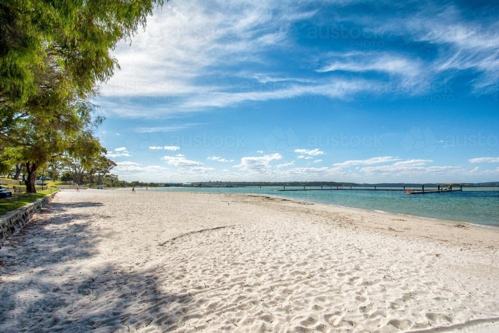 Day at the beach, shaded by trees - Australian Stock Image
