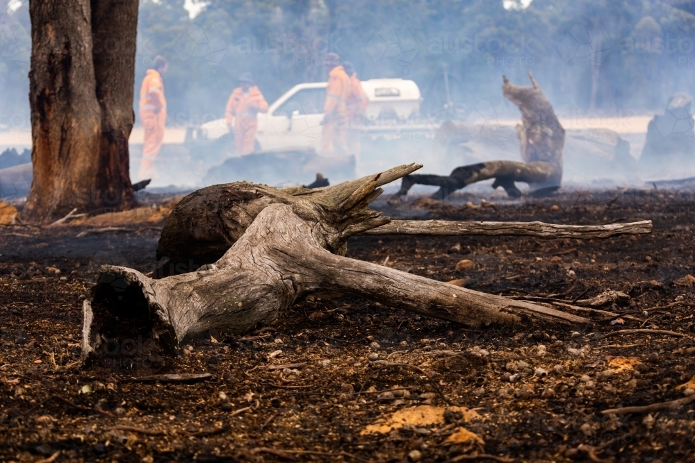 debris on foreground after a fire has been extinguished with firefighters in background - Australian Stock Image