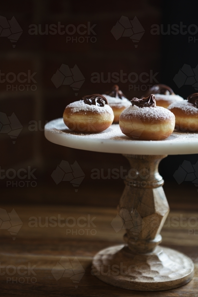 Delicious chocolate topped donuts on a vintage cake stand with space for recipe text - Australian Stock Image