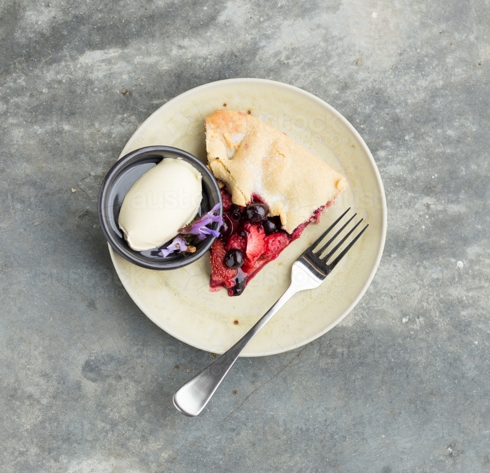 Dessert of strawberry and blueberry tart with cream on a concrete table - Australian Stock Image