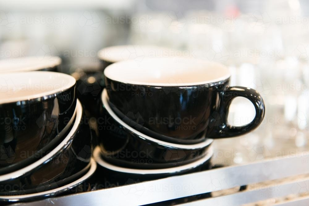 Detail of black coffee cups and glasses stacked in a cafe - Australian Stock Image