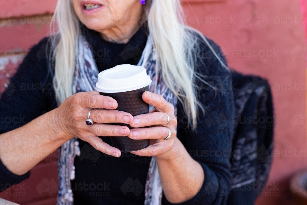 detail of older lady holding takeaway cup with two hands - Australian Stock Image