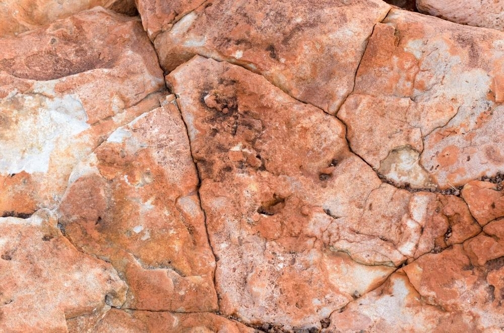 Detail shot of heavily textured pink, red and orange rock cracks and crevices - Australian Stock Image