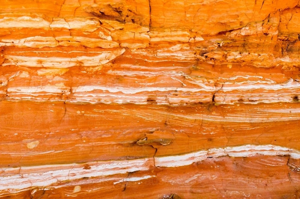 Detail shot of layered and patterned rock with orange, pink and yellow colours - Australian Stock Image