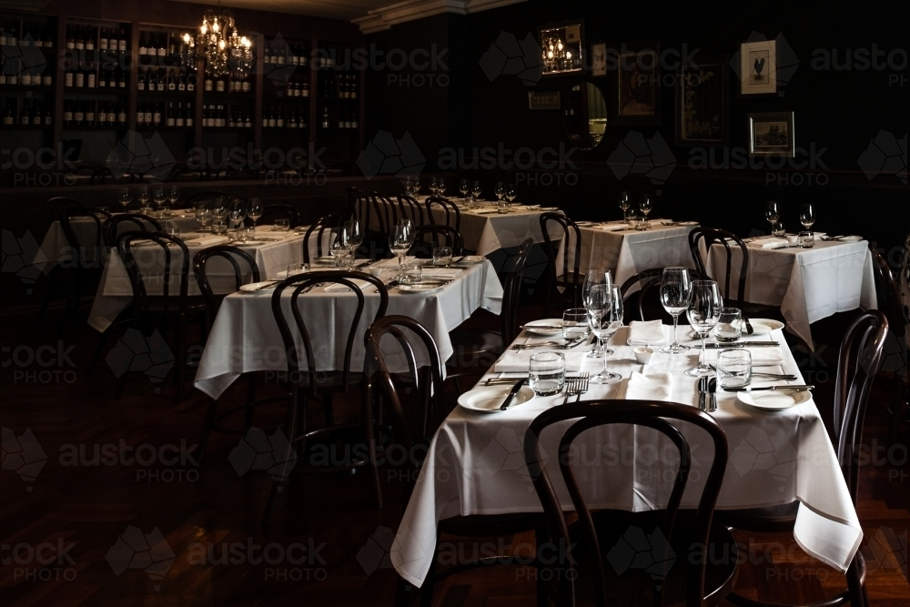 dim mood lighting in a restaurant with linen tablecloths and dinnerware laid out - Australian Stock Image