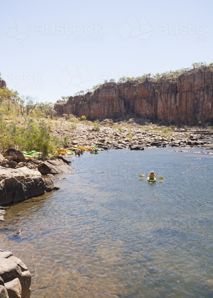 Distant people kayaking at remote gorge - Australian Stock Image