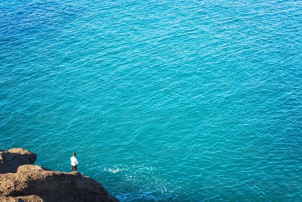 Distant person fishing off a rock beside clear blue sea waters - Australian Stock Image