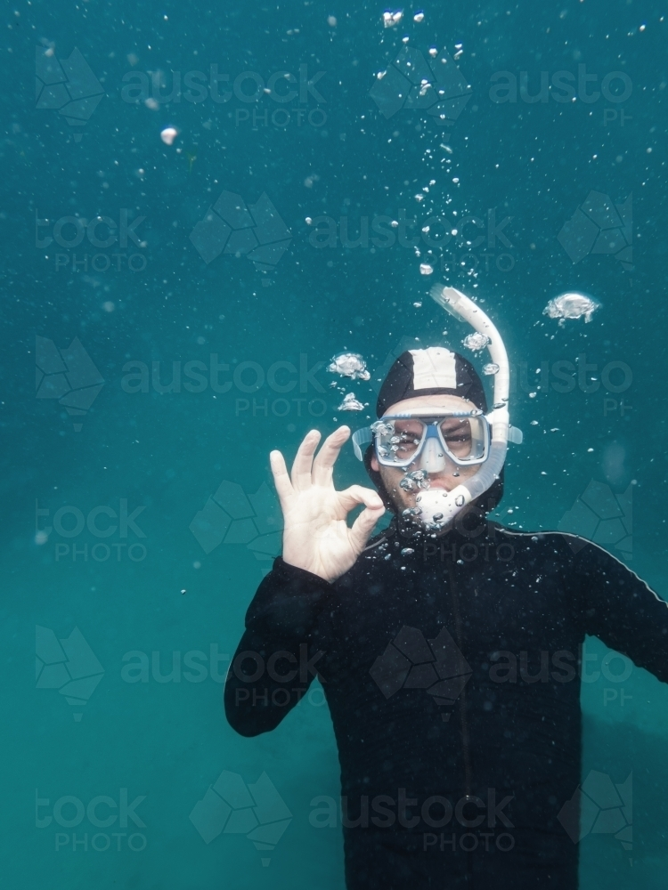Diver under water signalling he is ok via a hand gesture - Australian Stock Image