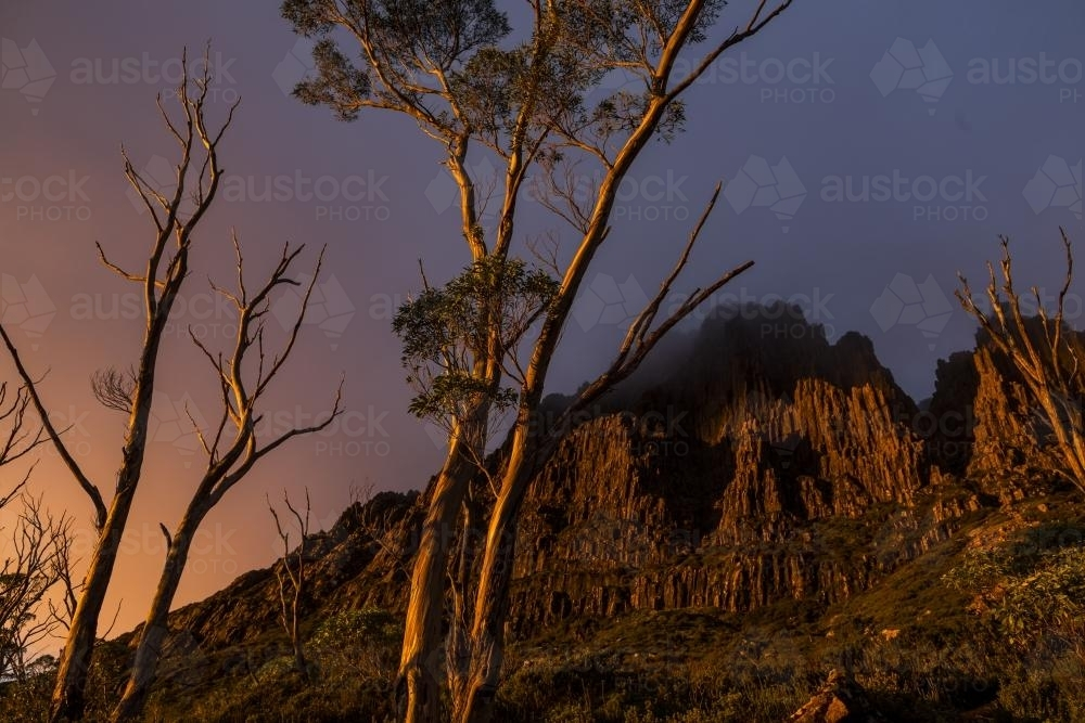 Dramatic sunset across the jagged flanks of Cradle Mountain - Australian Stock Image
