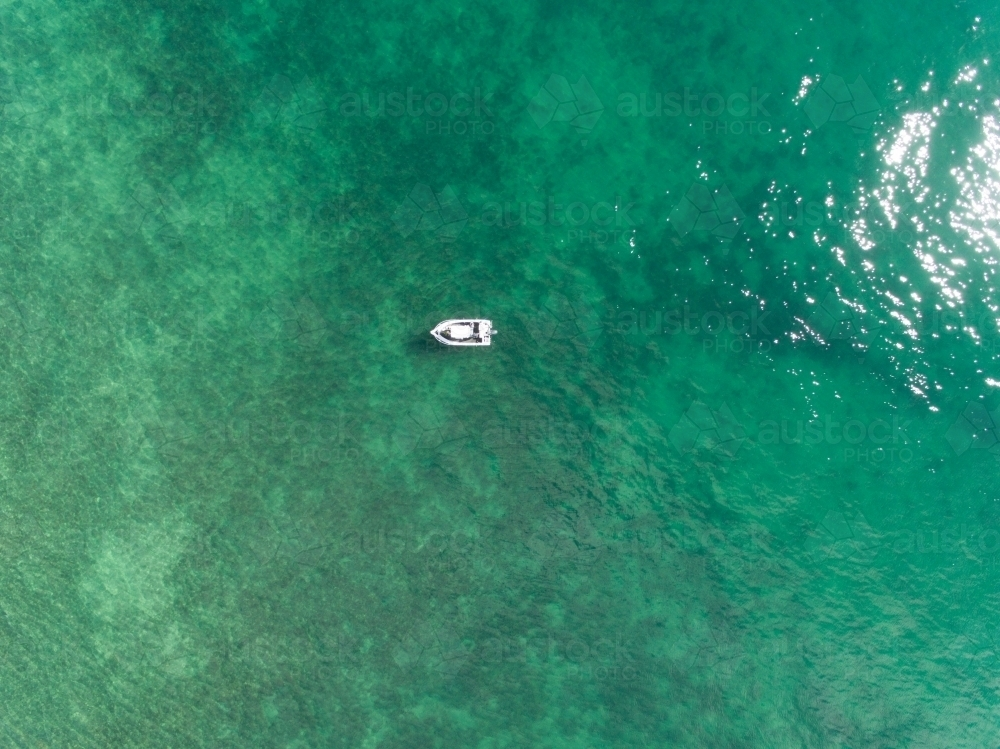 Drone image of a a small white boat in beautiful clear coastal waters - Australian Stock Image
