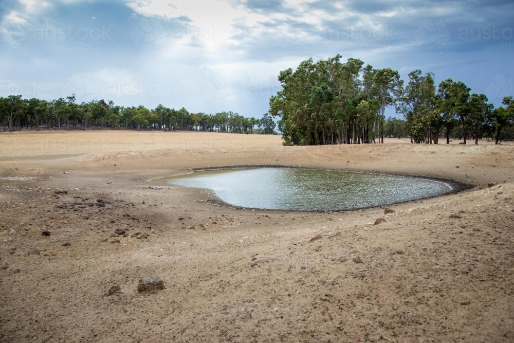 Dry farmland with small amount of water in dam - Australian Stock Image