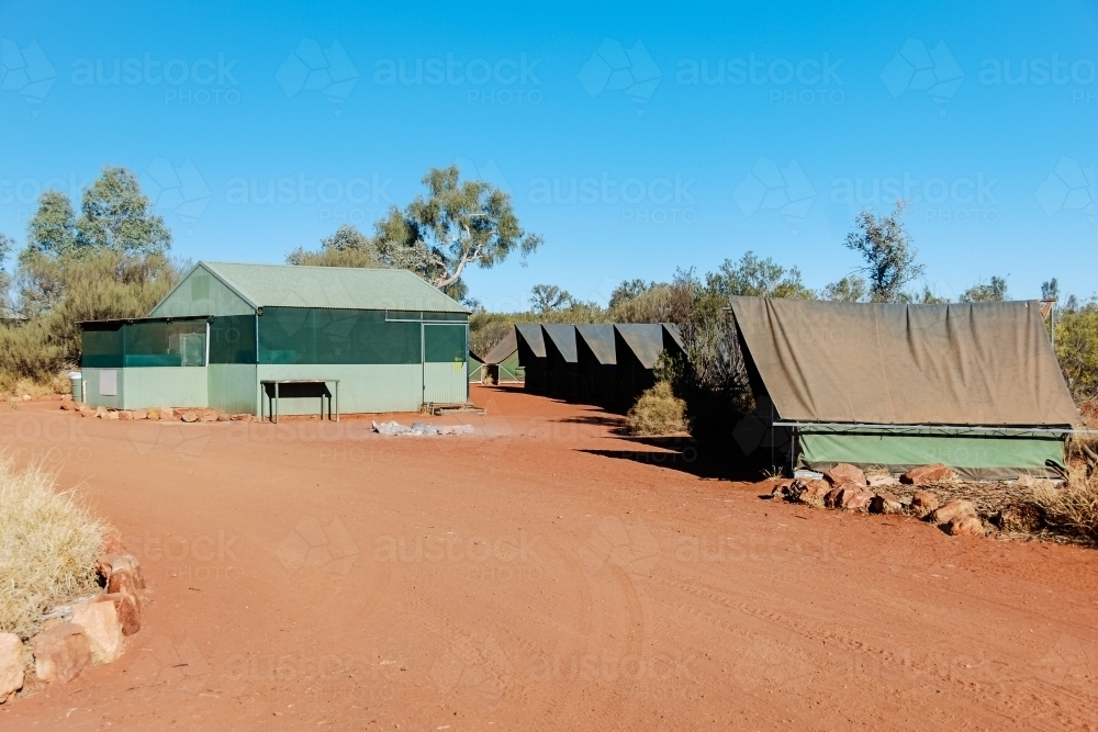 Dusty red dirt campsite in the outback with permanent tents - Australian Stock Image