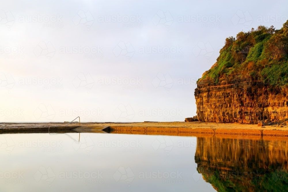 Early morning reflections in the Wombarra Rock Pool on the Illawarra Coast - Australian Stock Image