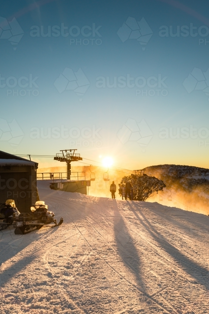 earlybird skiers heading down the slopes, silhouetted against the rising sun - Australian Stock Image