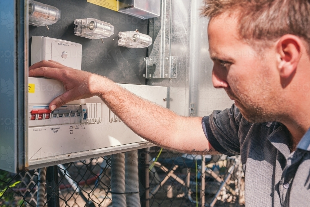 Electrician checking switches at the power box - Australian Stock Image