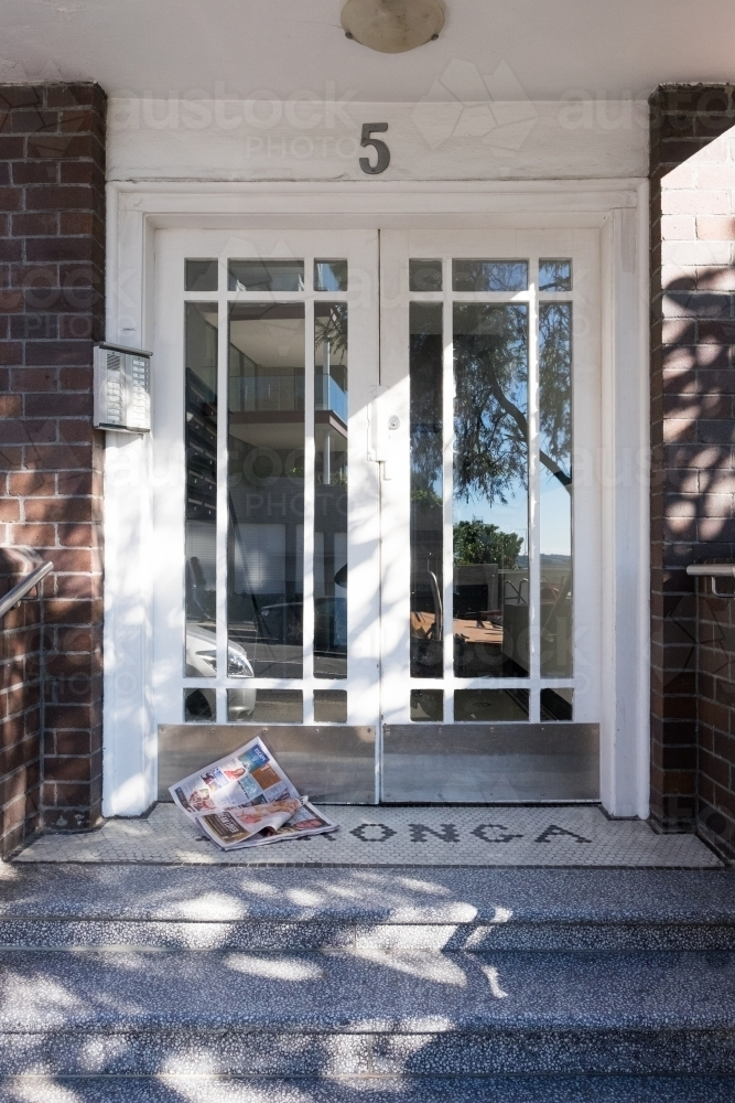 image of entrance to mid century apartment building with magazine by